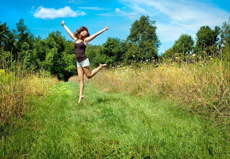 Ευτυχής γυναίκα που πηδά σε ένα πεδίο στοκ εικόνες με δικαίωμα ελεύθερης χρήσης