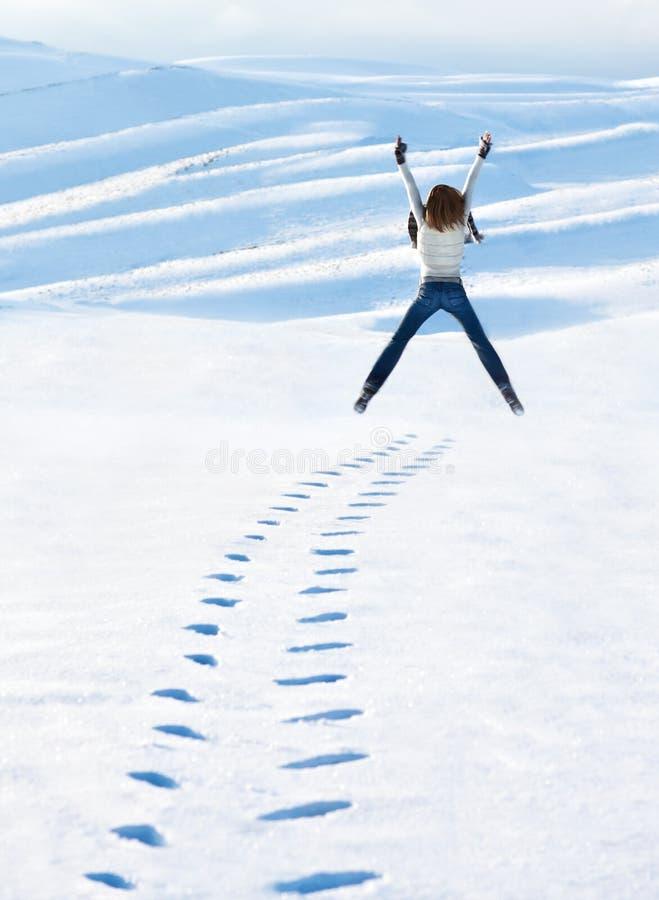 Ευτυχής γυναίκα που πηδά στα χειμερινά βουνά στοκ φωτογραφία