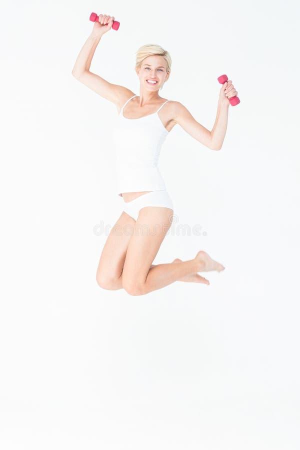 Ευτυχής γυναίκα που πηδά και που κρατά τους αλτήρες στοκ εικόνες