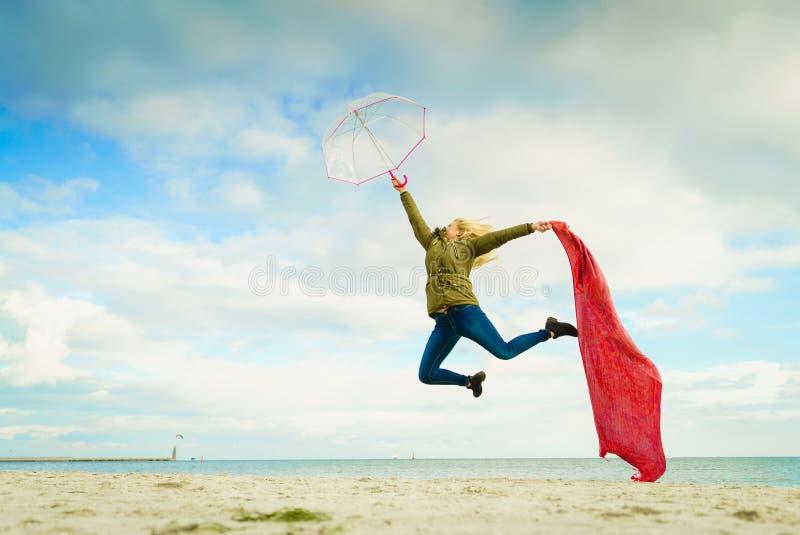 Ευτυχής γυναίκα που πηδά με το μαντίλι στην παραλία στοκ εικόνες με δικαίωμα ελεύθερης χρήσης