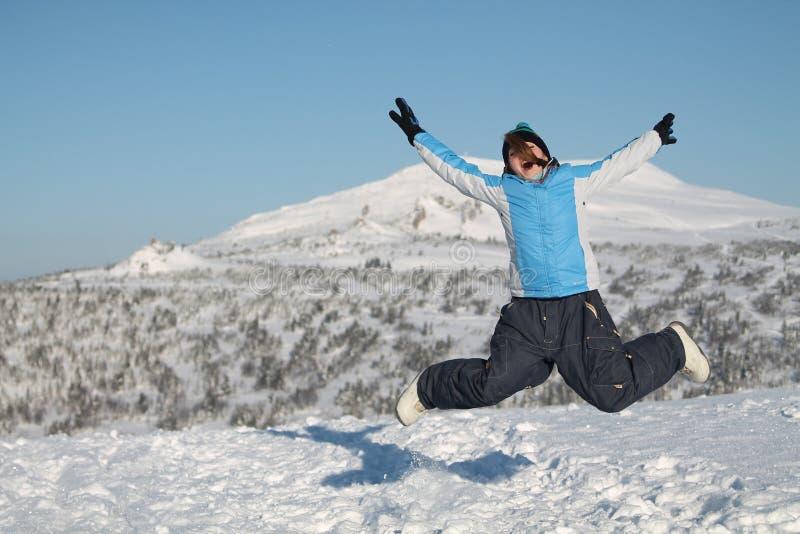Ευτυχής γυναίκα που πηδά στα χειμερινά βουνά, ενεργός θηλυκή φύση απόλαυσης, στοκ φωτογραφία