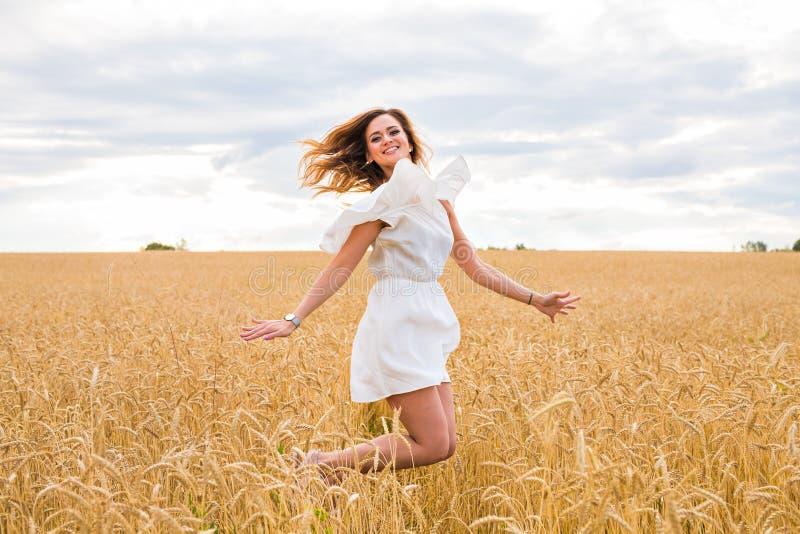 Ευτυχής γυναίκα που πηδά στον τομέα ενάντια στο μπλε ουρανό Έννοια διακοπών και ελευθερίας στοκ φωτογραφία με δικαίωμα ελεύθερης χρήσης