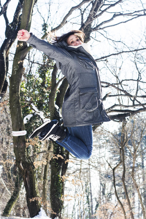 Ευτυχής γυναίκα που πηδά το χειμώνα στα ξύλα στοκ φωτογραφίες με δικαίωμα ελεύθερης χρήσης