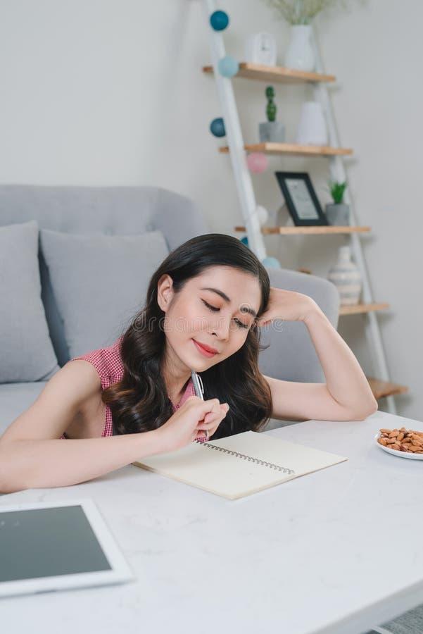 Ευτυχής γυναίκα που σκέφτεται τι για να γράψει σε μια συνεδρίαση σημειωματάριων στο floo στοκ εικόνες με δικαίωμα ελεύθερης χρήσης