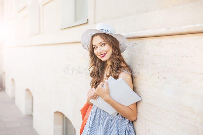 Ευτυχής γυναίκα που στέκεται και που κρατά δύο καλυμμένα κενό περιοδικά στοκ εικόνα
