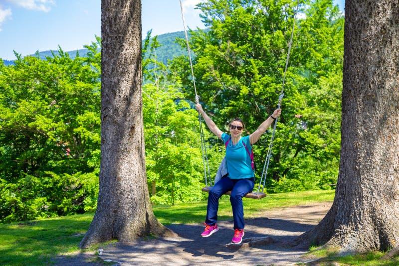 Ευτυχής γυναίκα που στέκεται σε μια ταλάντευση μεταξύ των δέντρων στοκ εικόνα με δικαίωμα ελεύθερης χρήσης