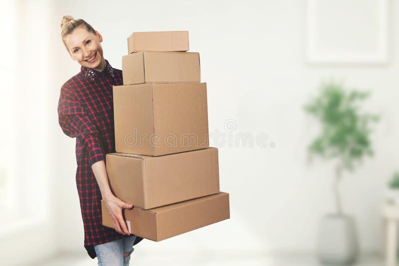 Ευτυχής γυναίκα που στέκεται στο καινούργιο σπίτι με τα ανήκοντας κιβώτια στα χέρια στοκ εικόνες