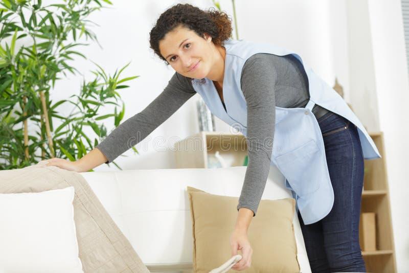 Ευτυχής γυναίκα που τακτοποιεί το ακατάστατο δωμάτιο στοκ φωτογραφία με δικαίωμα ελεύθερης χρήσης