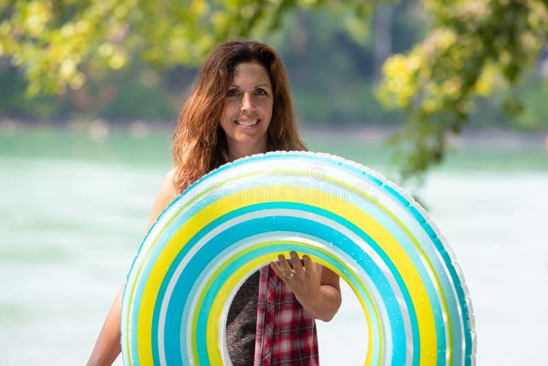 Ευτυχής γυναίκα που φέρνει διογκώσιμο innertube στοκ φωτογραφίες