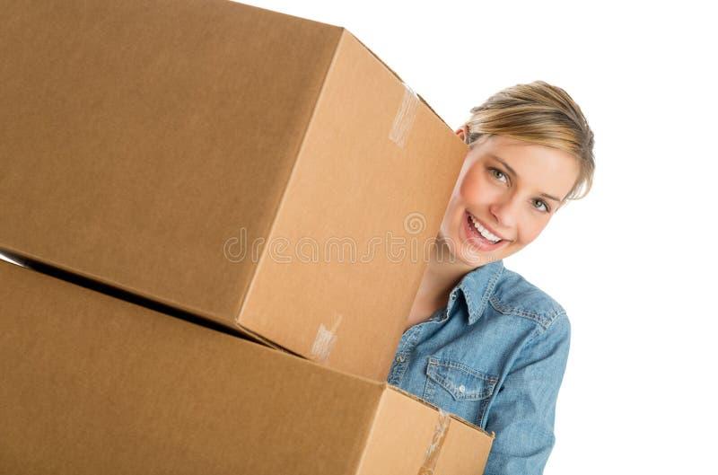 Ευτυχής γυναίκα που φέρνει τα συσσωρευμένα κουτιά από χαρτόνι στοκ εικόνα