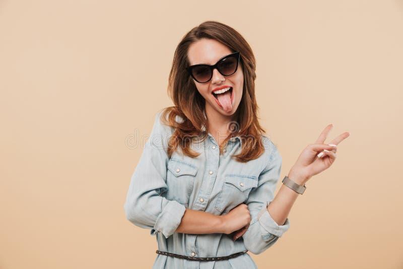 Ευτυχής γυναίκα που φορά τα γυαλιά ηλίου που παρουσιάζουν τη γλώσσα και χειρονομία ειρήνης στοκ φωτογραφία