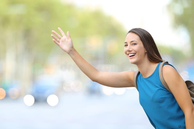 Ευτυχής γυναίκα που χαιρετά το αμάξι ταξί στην οδό στοκ φωτογραφίες με δικαίωμα ελεύθερης χρήσης
