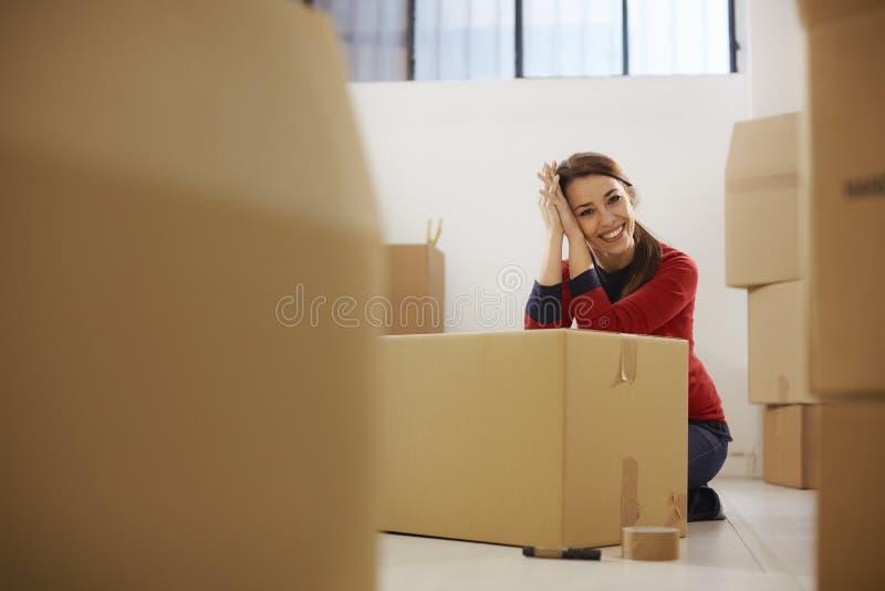 Ευτυχής γυναίκα που χαμογελά στο σπίτι κατά τη διάρκεια της κίνησης με τα κιβώτια στοκ εικόνες με δικαίωμα ελεύθερης χρήσης
