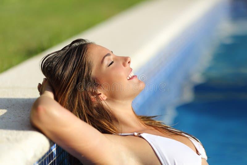 Ευτυχής γυναίκα που χαλαρώνουν σε μια πισίνα που απολαμβάνει τις διακοπές στοκ φωτογραφία με δικαίωμα ελεύθερης χρήσης
