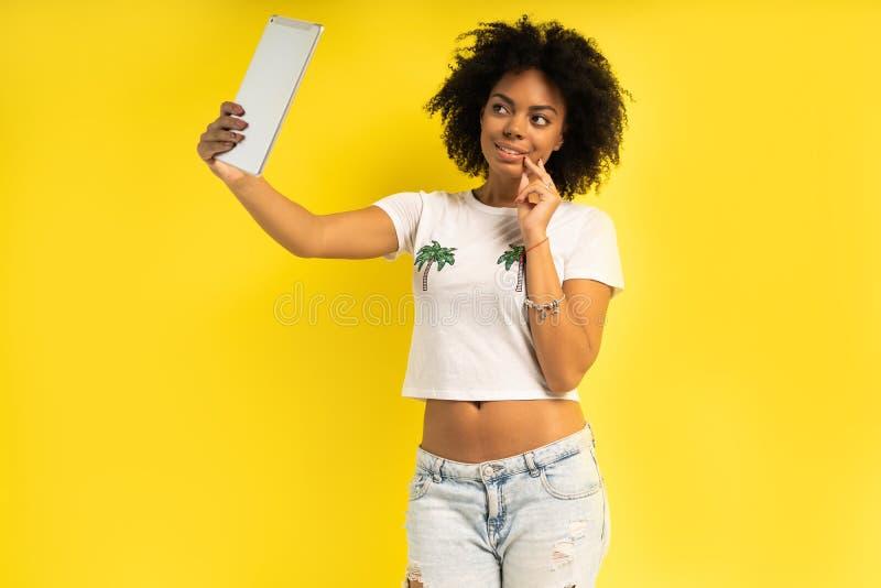 Ευτυχής γυναίκα που χρησιμοποιεί την ταμπλέτα για το βίντεο αλληλεπίδρασης που καλεί απομονωμένο στο κίτρινο υπόβαθρο στοκ φωτογραφία με δικαίωμα ελεύθερης χρήσης