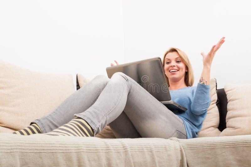 Ευτυχής γυναίκα που χρησιμοποιεί το lap-top στο σπίτι στον καναπέ στοκ εικόνα με δικαίωμα ελεύθερης χρήσης