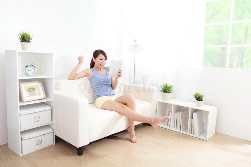 Ευτυχής γυναίκα που χρησιμοποιεί το PC ταμπλετών στον καναπέ στοκ εικόνα