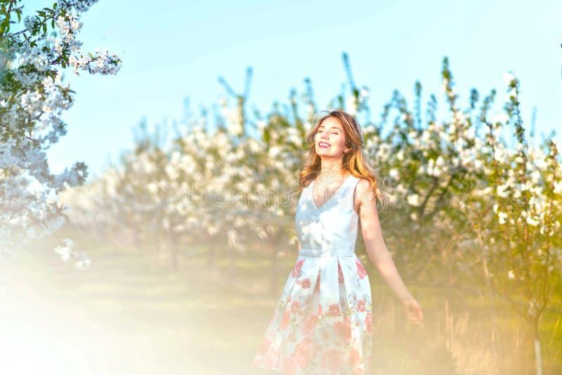Ευτυχής γυναίκα σε έναν οπωρώνα στην άνοιξη Απόλαυση της ηλιόλουστης θερμής ημέρας Αναδρομικό φόρεμα ύφους Ανθίζοντας δέντρα κερα στοκ εικόνες