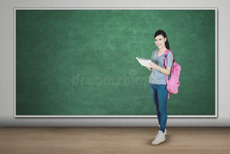 Ευτυχής γυναίκα σπουδαστής που χρησιμοποιεί την ταμπλέτα στην τάξη στοκ φωτογραφία