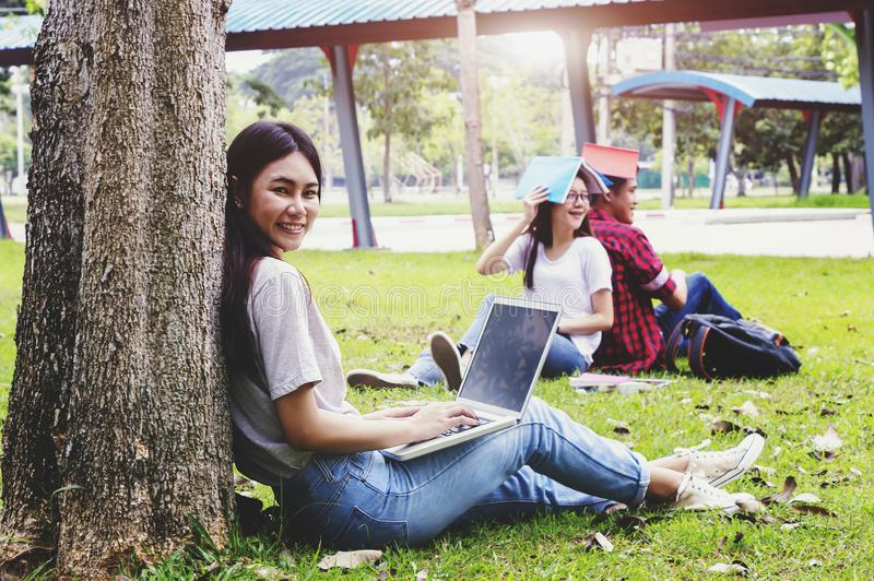 Ευτυχής γυναίκα σπουδαστής που χρησιμοποιεί το lap-top της υπαίθρια με μια ομάδα ανθρώπων στο υπόβαθρο στοκ εικόνες με δικαίωμα ελεύθερης χρήσης