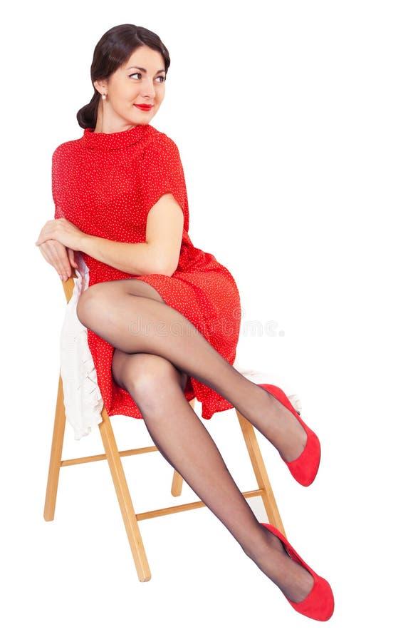 Ευτυχής γυναίκα στην κόκκινη συνεδρίαση φορεμάτων σε μια καρέκλα στοκ φωτογραφία με δικαίωμα ελεύθερης χρήσης