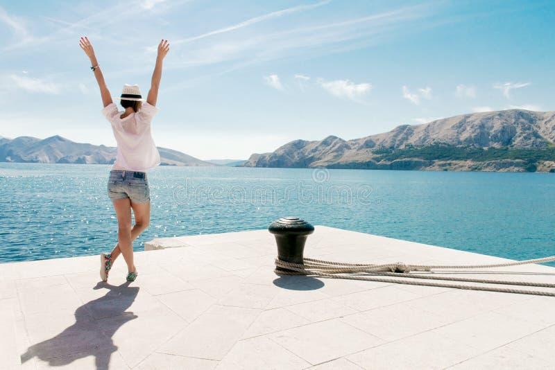 Ευτυχής γυναίκα στις διακοπές που υπερασπίζονται τη θάλασσα όπλα που αυξάνονται Το ξένοιαστο νέο θηλυκό απολαμβάνει τις διακοπές στοκ φωτογραφίες με δικαίωμα ελεύθερης χρήσης
