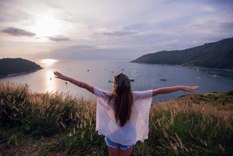 Ευτυχής γυναίκα στο ηλιοβασίλεμα στη φύση το καλοκαίρι με τα ανοικτά χέρια στοκ φωτογραφία με δικαίωμα ελεύθερης χρήσης