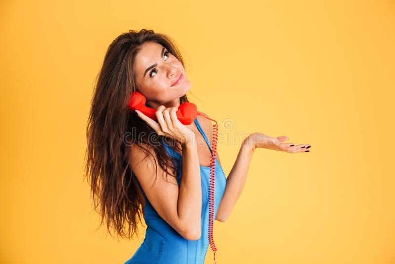 Ευτυχής γυναίκα στο μαγιό που μιλά στο τηλέφωνο πέρα από το πορτοκαλί υπόβαθρο στοκ φωτογραφίες