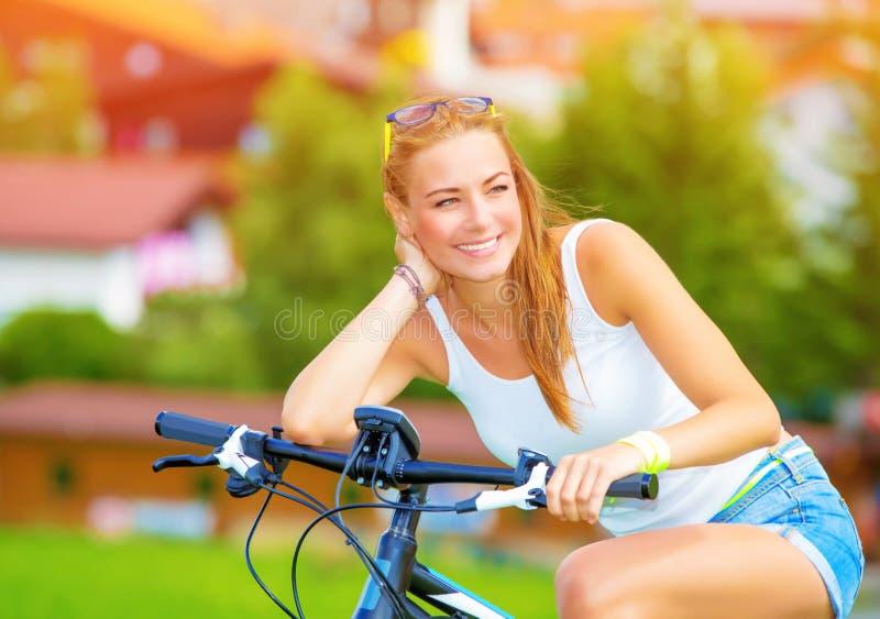 Ευτυχής γυναίκα στο ποδήλατο στοκ φωτογραφίες
