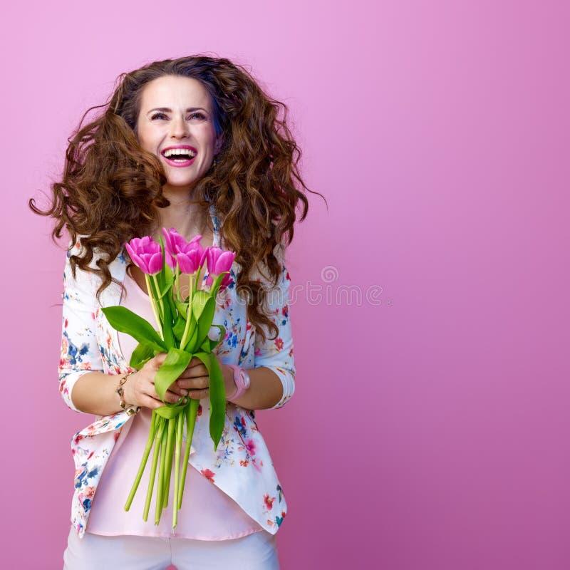 Ευτυχής γυναίκα στο ρόδινο υπόβαθρο με την ανθοδέσμη του άλματος λουλουδιών στοκ εικόνες