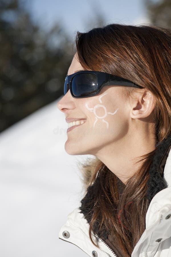Ευτυχής γυναίκα στο χιόνι με έναν μικρό ήλιο στο μάγουλό της στοκ εικόνες