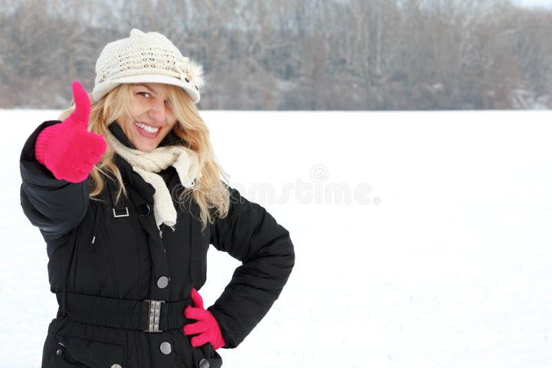 Ευτυχής γυναίκα στο χιόνι που εξετάζει επάνω τη κάμερα με τον αντίχειρα επάνω στοκ φωτογραφία
