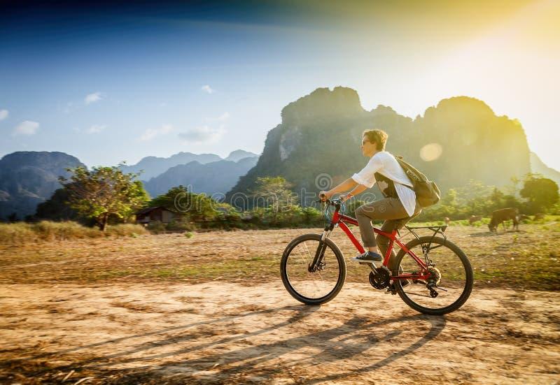 Ευτυχής γυναίκα τουριστών που οδηγά ένα ποδήλατο στην περιοχή βουνών στο Λάος Τ στοκ εικόνα με δικαίωμα ελεύθερης χρήσης