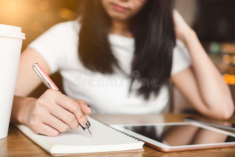 Ευτυχής γυναίκα φοιτητών πανεπιστημίου χαμόγελου με τη μάνδρα που γράφει στο σημειωματάριο ι στοκ φωτογραφία με δικαίωμα ελεύθερης χρήσης