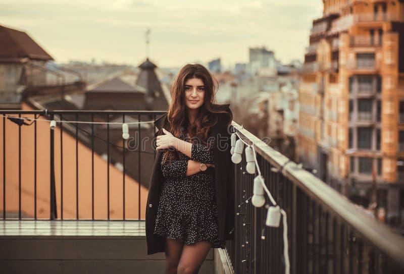 Ευτυχής γυναίκα brunette που στέκεται στη στέγη πέρα από τη σύγχρονη πόλη  στοκ εικόνες