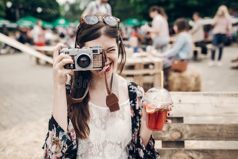 ευτυχής γυναίκα hipster στα γυαλιά ηλίου που κάνει τη φωτογραφία με την παλαιά κάμερα α στοκ εικόνα με δικαίωμα ελεύθερης χρήσης
