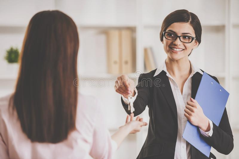 Ευτυχής γυναίκα realtor που δίνει το κλειδί σε έναν καινούργιο ιδιοκτήτη ενός διαμερίσματος στοκ φωτογραφίες με δικαίωμα ελεύθερης χρήσης