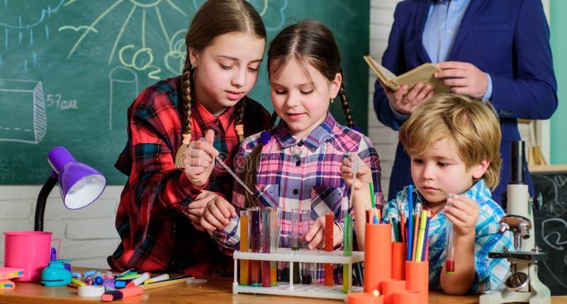 Ευτυχής δάσκαλος παιδιών o παιδιά στη χημεία εκμάθησης παλτών εργαστηρίων στο σχολικό εργαστήριο να κάνει τα πειράματα με στοκ εικόνες