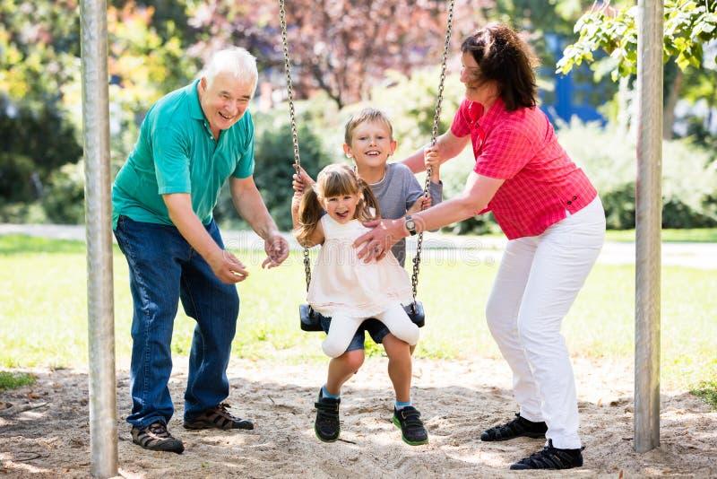 Ευτυχής εγγονή που προετοιμάζεται για την ταλάντευση με τον παππού και γιαγιά τους στοκ φωτογραφία
