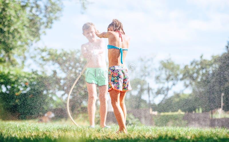 Ευτυχής εικόνα έννοιας παιδικής ηλικίας Δύο childs που παίζουν στον κήπο, χύνουν το ένα το άλλο από τη μάνικα, κάνουν μια βροχή στοκ εικόνες