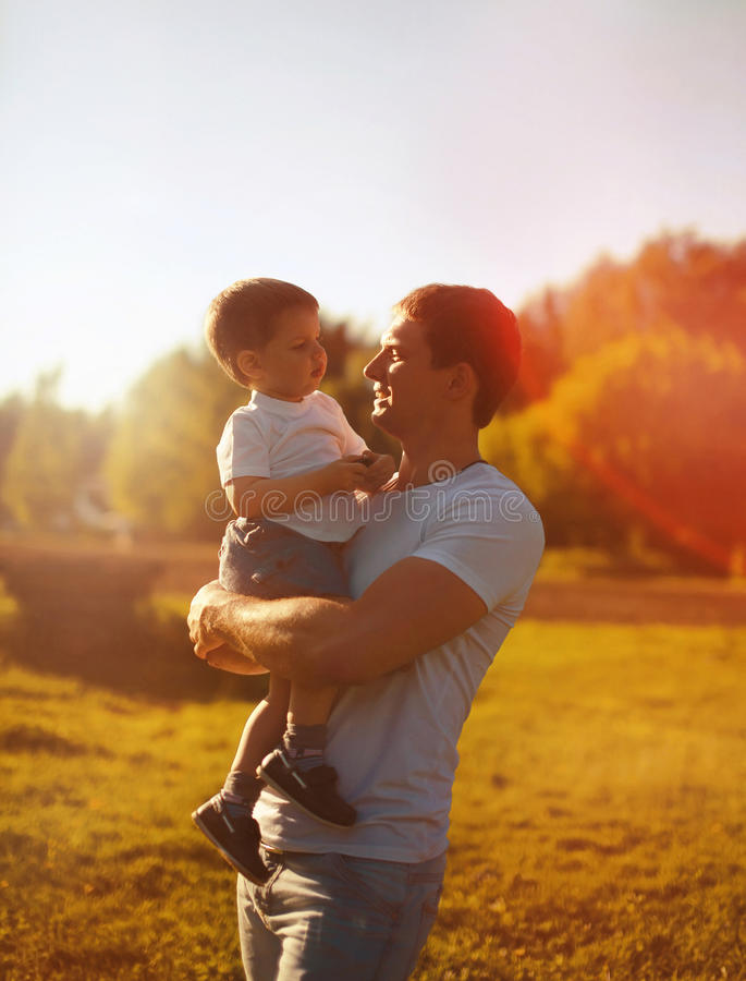 Ευτυχής εκμετάλλευση πατέρων στο θερμό βράδυ φθινοπώρου γιων παιδιών χεριών, ηλιόλουστη οικογενειακή φωτογραφία στοκ φωτογραφίες