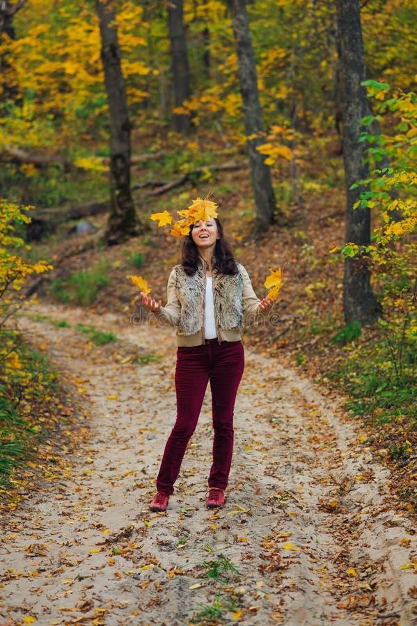 Ευτυχής εκτίναξη γυναικών επάνω στα φύλλα φθινοπώρου στοκ εικόνα με δικαίωμα ελεύθερης χρήσης