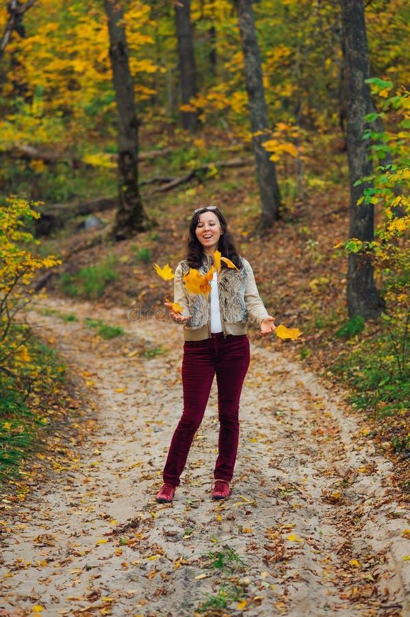 Ευτυχής εκτίναξη γυναικών επάνω στα φύλλα φθινοπώρου στοκ εικόνα