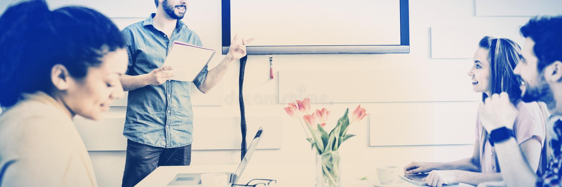 Ευτυχής εκτελεστική δίνοντας παρουσίαση στους συναδέλφους στην αίθουσα συνεδριάσεων στο δημιουργικό γραφείο στοκ φωτογραφίες