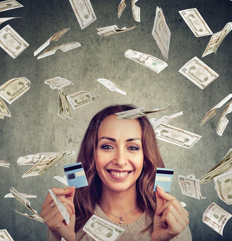 Ευτυχής ελεύθερη γυναίκα χρέους που κρατά μια πιστωτική κάρτα κομμένη σε δύο κομμάτια στοκ εικόνα