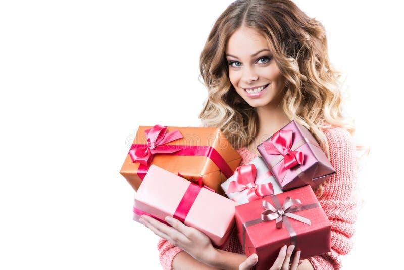 Ευτυχής ελκυστική γυναίκα που κρατά το μεγάλο σωρό των δώρων στοκ φωτογραφία