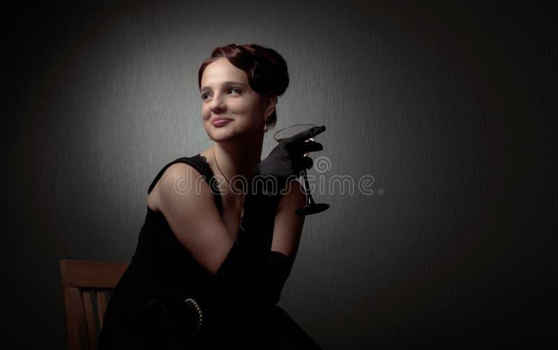 Ευτυχής ελκυστική γυναίκα στο μαύρο φόρεμα με το τέλειο γυαλί τρίχας και makeup εκμετάλλευσης martini στοκ εικόνες