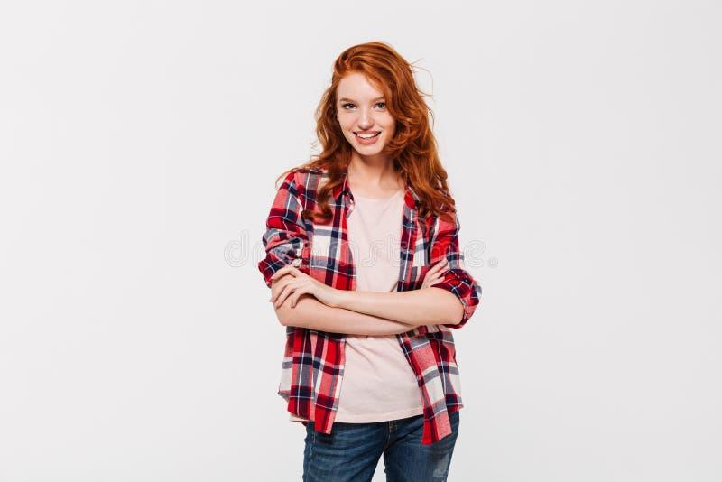 Ευτυχής ελκυστική νέα redhead κυρία με τα όπλα που διασχίζονται κάμερα στοκ φωτογραφία