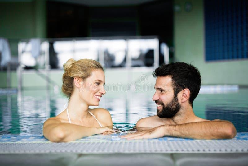 Ευτυχής ελκυστική χαλάρωση ζευγών στην πισίνα στοκ εικόνες