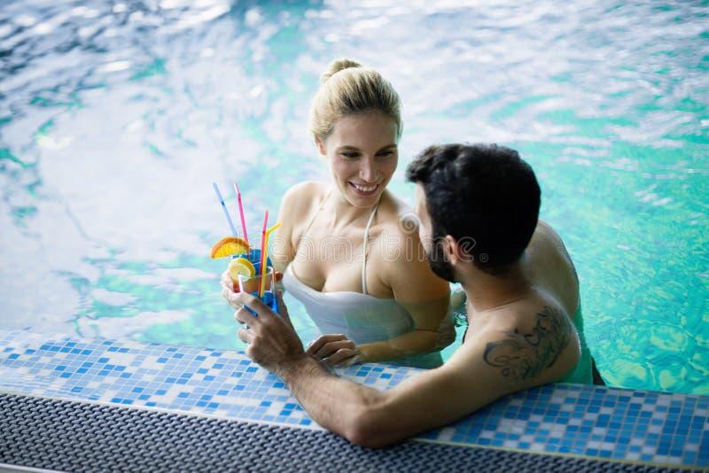 Ευτυχής ελκυστική χαλάρωση ζευγών στην πισίνα στοκ φωτογραφίες με δικαίωμα ελεύθερης χρήσης